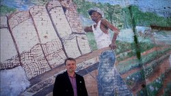 Reporter Chris Tomlinson stands in front of a mural.
