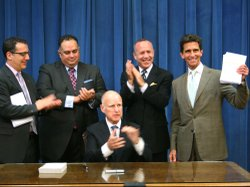Calif. Gov. Jerry Brown signs the 2013-14 state budget, as Democratic legislative leaders and Budget Committee chairs watch, June 27, 2013.