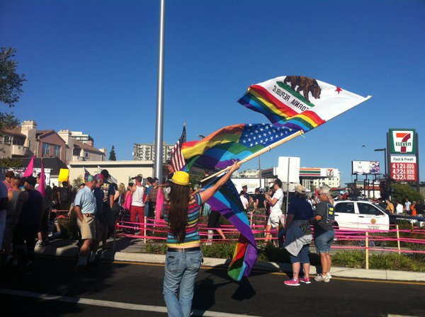 A woman waves the California state flag and an American flag with rainbow str...
