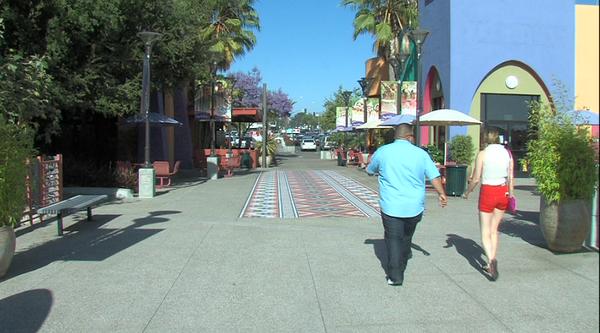 People walk on the mosaic of tiles at Market Creek Plaza.