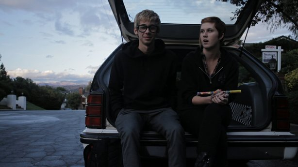 Garrison and Skye sit in the back of a car.