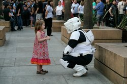 A stormtrooper reenactor greets a young girl during an appearance.