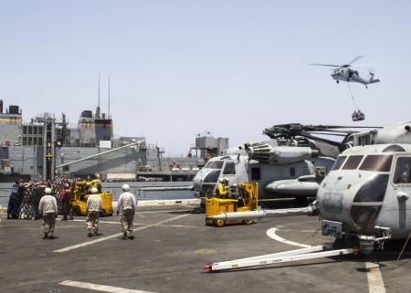 A U.S. Navy MH-60S Seahawk helicopter transports food and supplies to the USS...