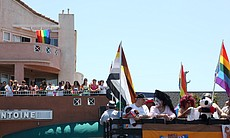 Spectators watch from a balcony on Normal Street as floats pass by in the San Diego Pride Parade, July 13, 2013.