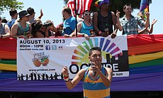 A San Diego Pride Parade participant dances alongside a float on University Avenue, July 13, 2013.