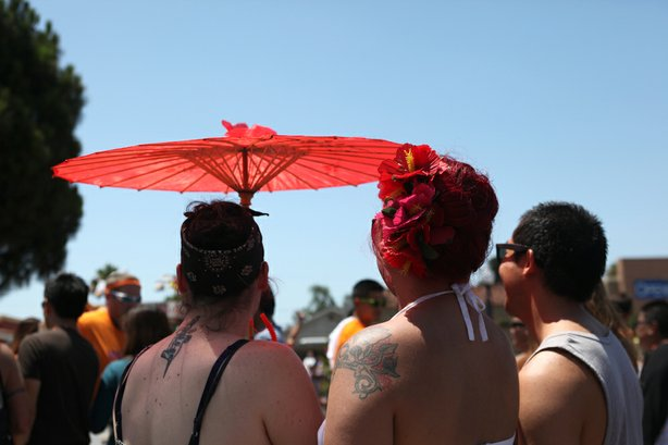 San Diego Pride attendees use parasols to shade themselves beneath the day's heat, July, 13, 2013.