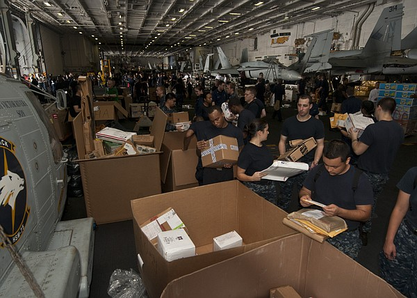 Sailors sort mail aboard the aircraft carrier USS Nimitz while conducting a r...