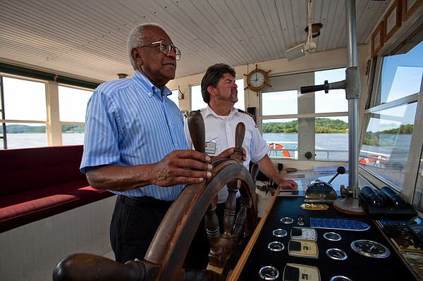Sir Trevor McDonald takes the wheel of a riverboat with the help of the capta...