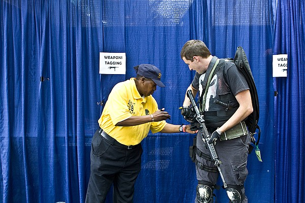 A Comic-Con attendee gets one of his fake weapons inspected.