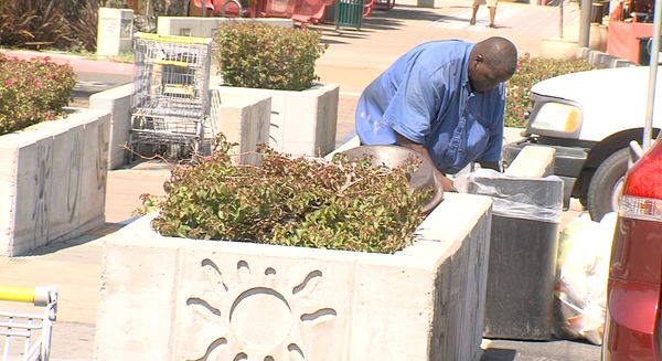 A man helps clean up the parking lot in Market Creek Plaza.