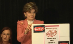 Attorney Gloria Allred holds up the warning sign she proposes the city of San Diego hang outside the mayor's office.