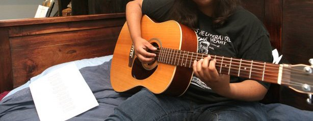 Rehana Faruqi plays guitar in her room. Music is a comforting to this young M...
