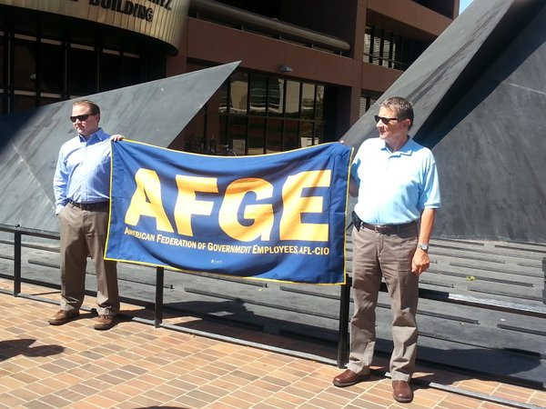 Members of the American Federation of Government Employees hold an AFGE banne...
