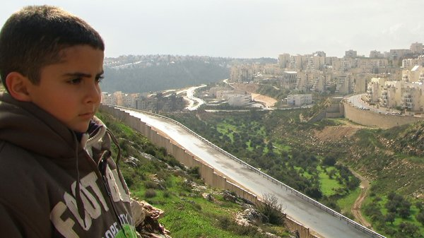 Emad Burnat's son Gibreel and the wall.