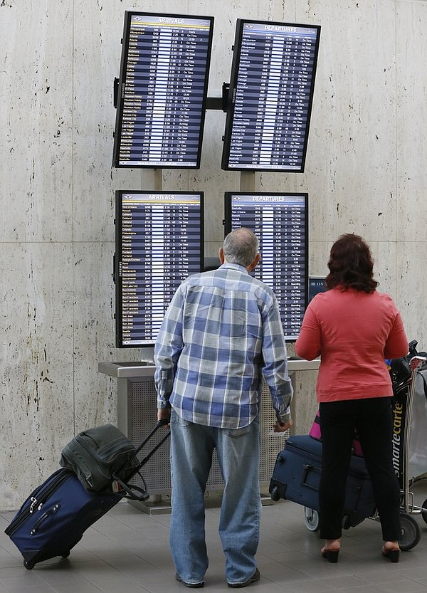 Passengers check their flight status at Los Angeles International Airport