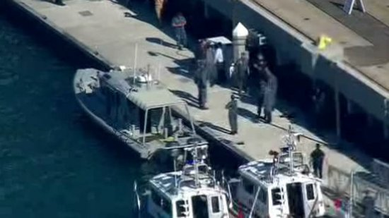 Law enforcement surrounds Navy boat where shooting took place.