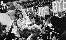 Ms. Billie Jean King waves to crowds at the Astrodome in Houston, Texas, September 20,1973 as she is borne onto the crowd on a multicolored throne carried by four men for her match with Bobby Riggs.