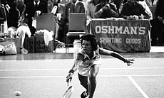 Billie Jean King bends down low to send the bal...