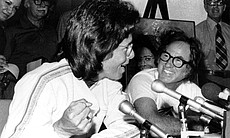 Tennis player Billie Jean King, left, makes a fist while she answers a question at a news conference in Houston, Texas, on Wednesday, Sept. 20, 1973. At right is Bobby Riggs smiling as King answers.