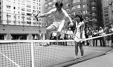Wimbledon Champ Billie Jean King holds down the net as Bobby Riggs, the 55-year-old tennis player who bested Margaret Court in a grudge match, jumps over the net in New York on July 11, 1973. King and Riggs announced that they will meet in similar $100,000 tennis match at a time and place as yet unannounced. Mrs. King is 26 years his junior.