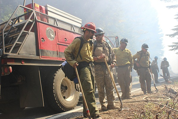 A Del Rosa hotshot and Elk Creek firefighters stand amid smoke from the Rim F...