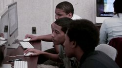 "Students working at computers as featured in ""Is School Enough?"""