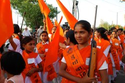 14-year-old Chinmayee poses with a rifle at the Durga Camp graduation ceremony.