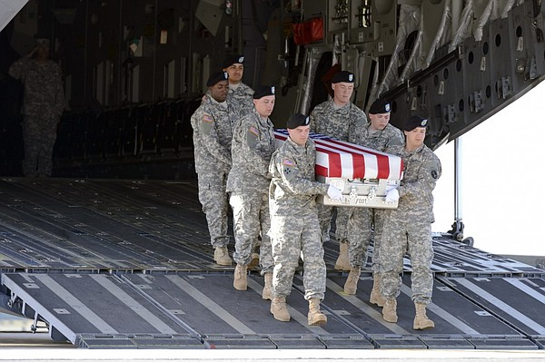 A U.S. Army carry team transfers the remains of Staff Sgt...