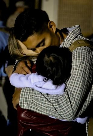 Lance Cpl. Ernesto Menjivar hugs his wife, Ashley, and daughter, Lucy, before...