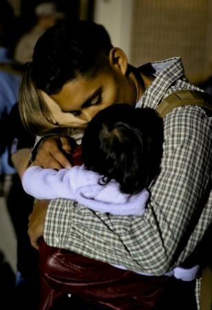 Lance Cpl. Ernesto Menjivar hugs his wife, Ashley, and daughter, Lucy, before leaving on deployment Sept. 14, 2013.