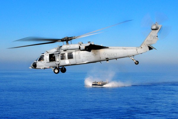 An MH-60S Knighthawk helicopter flies over the Pacific Oc...
