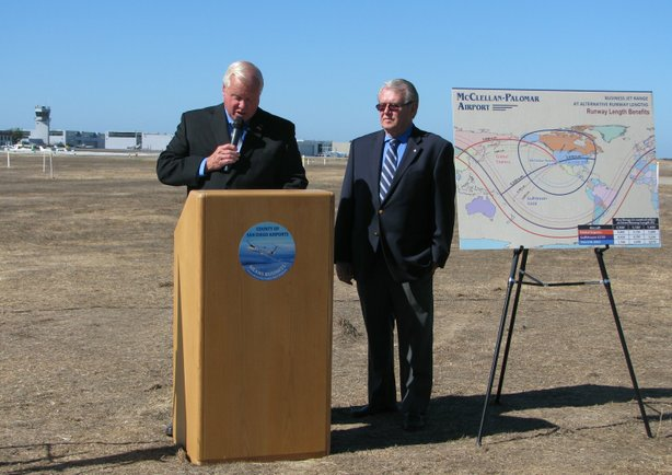 San Diego Supervisor Bill Horn and Carlsbad Mayor Matt Hall announcing the results of a feasibility study of expanding the runway at McClellan-Palomar Airport, Sept. 23, 2013. At right, a map shows how the reach of aircraft would expand to Asia if the runway were expanded 900 feet.