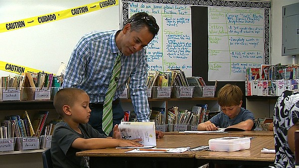 Ocean Beach Elementary Principal Marco Drapeau checks in on one of his school...