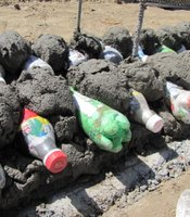 Plastic bottles filled with trash can function as fill space inside the structure of a bench or wall.