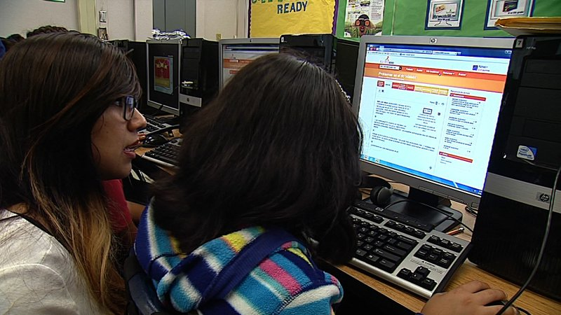 A Promise Neighborhood staff member works with students after school in the C...