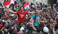 Protesters at the Arab Spring uprising in Egypt. A young man is wearing a Superman t-shirt in the crowd.