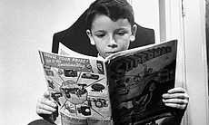 A young boy reading a Superman comic book, 1942.