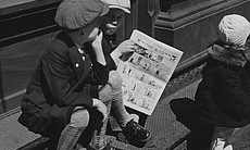 Two boys reading comics on a street corner, 1933.