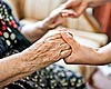 An elderly woman holds hands with a younger per...