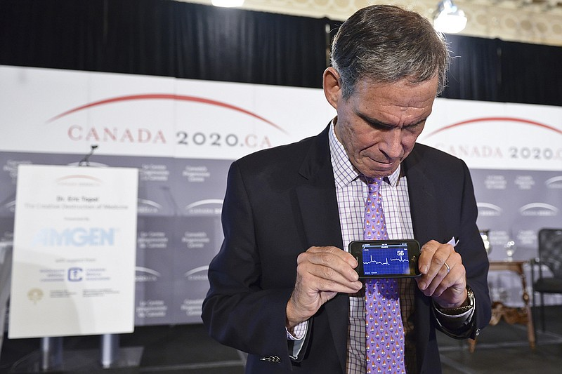 Dr. Eric Topol demonstrates a mobile health app on a smartphone.