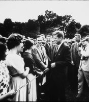 Rowland Scherman (with camera) photographing John F. Kennedy.