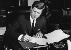 President Kennedy signs the Interdiction of the Delivery of Offensive Weapons to Cuba Proclamation, October 23, 1962, at the White House.