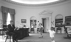 President John F. Kennedy claps while his children Caroline and John, Jr. dance in the Oval Office.