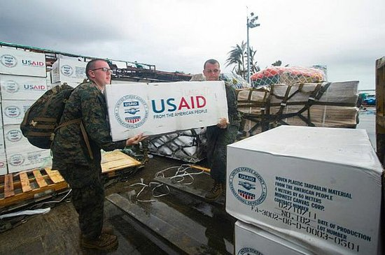 Hospital Corpsman 3rd Class Eric Chiarito, left, and Marine Sgt. Jonathan Thornton load supplies at Tacloban Air Base in support of Operation Damayan.