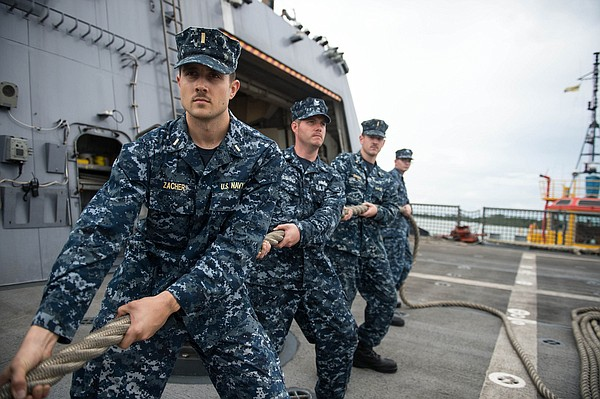 Sailors aboard USS Freedom participate in a line handling detail as the ship ...