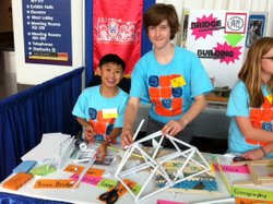 Caleb Leung (left) and Scully Randlett, 7th graders at Alice Fong Yu K-8 Chinese Immersion School in San Francisco, build a cantilever bridge Monday using paper rolls and scotch tape at the STEM Symposium in Sacramento.