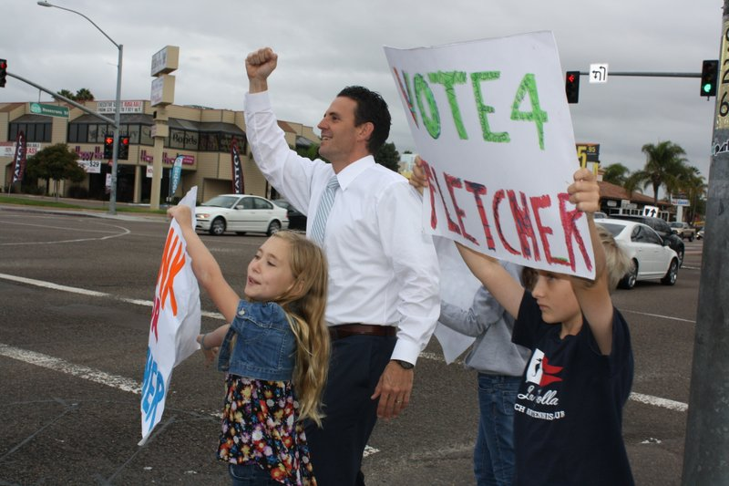 Nathan Fletcher and supporters stand on a street corner to rally voters for t...