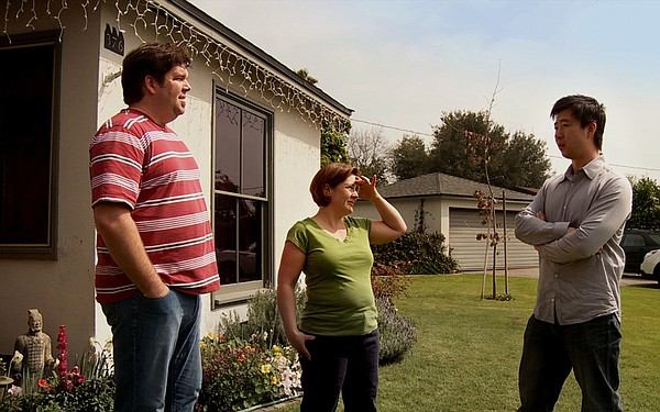 Tom Xia (right) visits his neighbors Evelyn and Tim Jones.