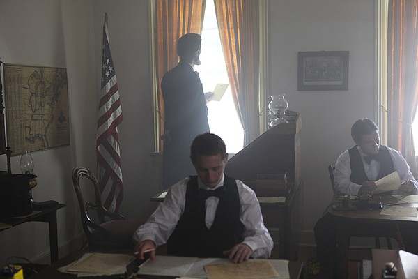 Lincoln reading a telegraph at the window of the telegraph office.