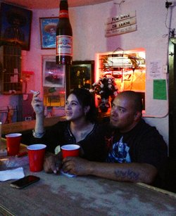 A couple watches a boxing match at The Brown Derby, the only bar in Santa Clara, New Mexico.